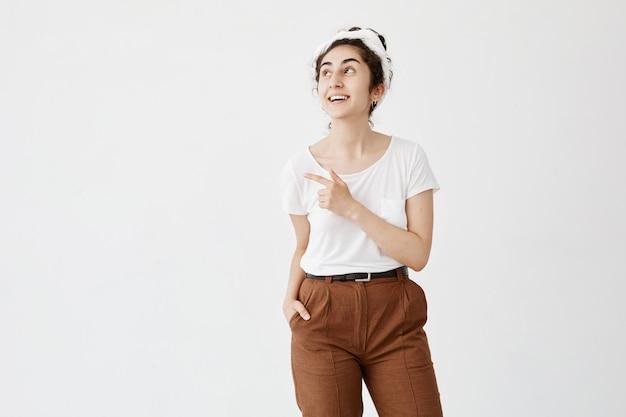 Mujer sonriente con cabello ondulado oscuro en moño en ropa casual posando contra la pared blanca apuntando al espacio de copia para su anuncio o texto. chica positiva con bollo de pelo publicidad algo