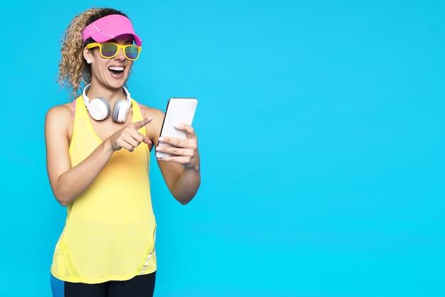 Mujer sonriente con cabello rizado rubio sosteniendo un teléfono contra un fondo azul.