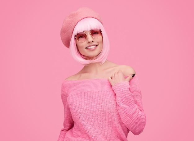 Mujer sonriente con cabello rosado mirando a la cámara
