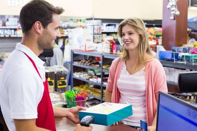 Mujer sonriente en caja registradora pagando con tarjeta de crédito y escanear un producto