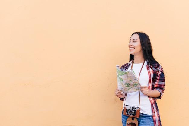Mujer sonriente con cámara alrededor de su cuello con mapa