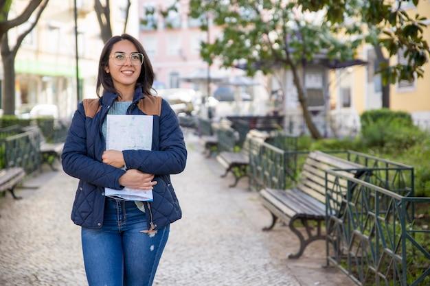 Mujer sonriente caminando al aire libre y sosteniendo el mapa doblado