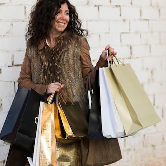 Mujer sonriente caminando con bolsas de compras