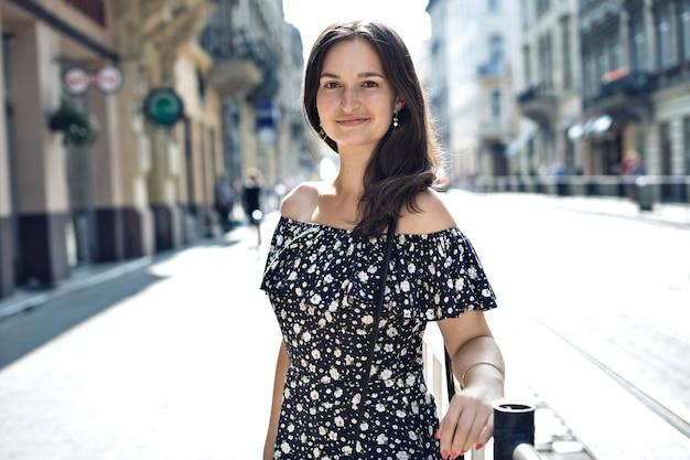 Mujer sonriente caminando en la concurrida calle de la ciudad