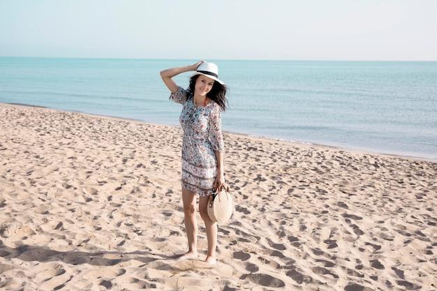 Mujer sonriente caminando a la orilla del mar