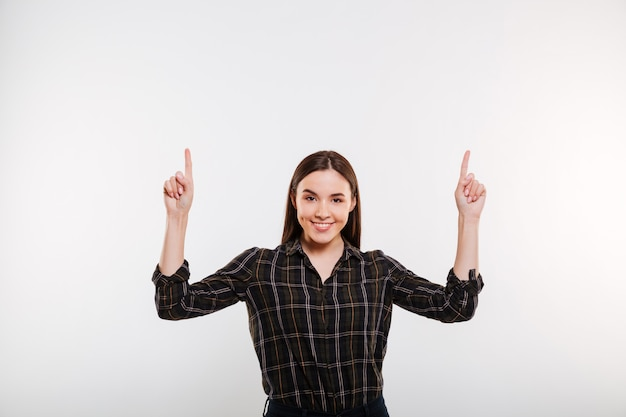 Mujer sonriente en camisa apuntando hacia arriba