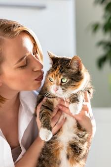 Mujer sonriente en camisa blanca besándose y abrazándose con ternura y amor gato, sosteniéndola en brazos