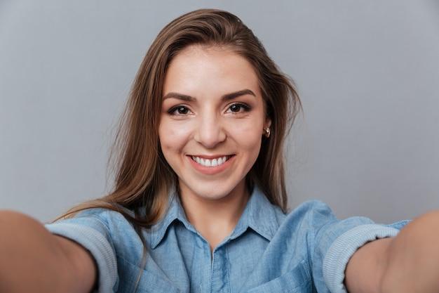 Mujer sonriente en camisa haciendo selfie en estudio