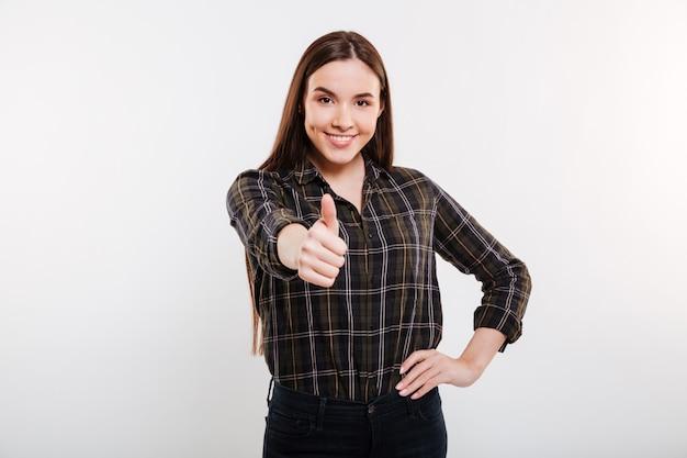 Mujer sonriente en camisa mostrando el pulgar hacia arriba