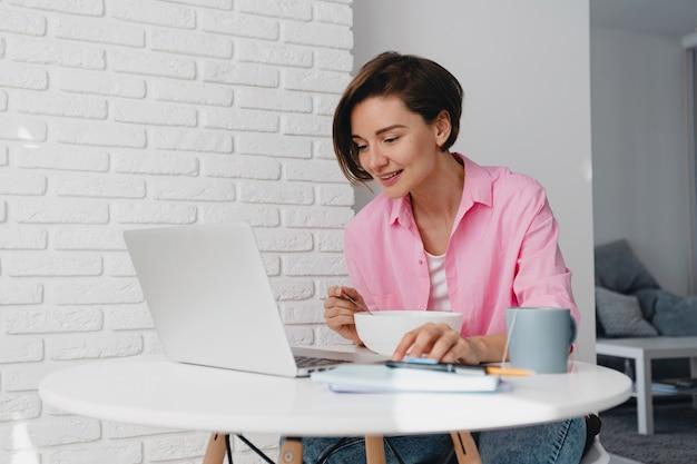 Mujer sonriente en camisa rosa desayunando en casa en la mesa trabajando en línea en el portátil desde casa, comiendo cereales