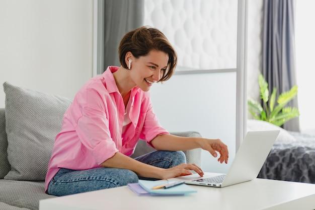 Mujer sonriente en camisa rosa sentado relajado en el sofá en casa en la mesa trabajando en línea en la computadora portátil desde casa