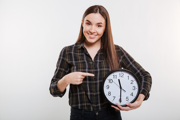 Mujer sonriente en camisa sosteniendo el reloj