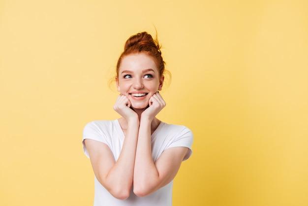 Mujer sonriente en camiseta se reclina en las manos y mirando a otro lado
