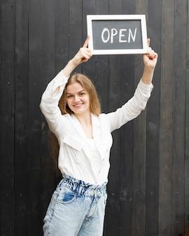 Mujer sonriente con cartel abierto