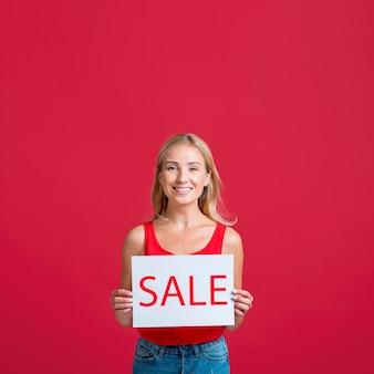 Mujer sonriente con cartel de venta con espacio de copia