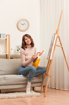 Mujer sonriente en casa pintando