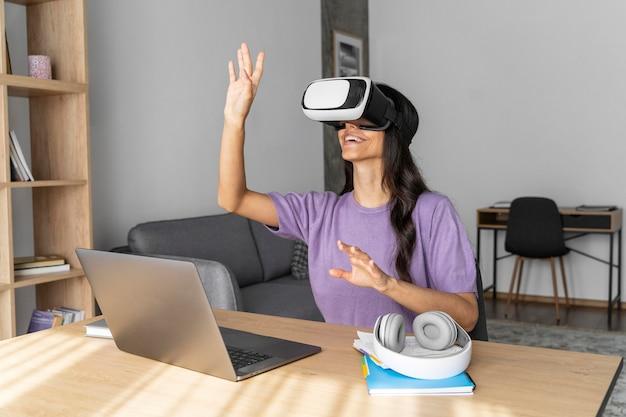 Mujer sonriente con casco de realidad virtual en casa con portátil