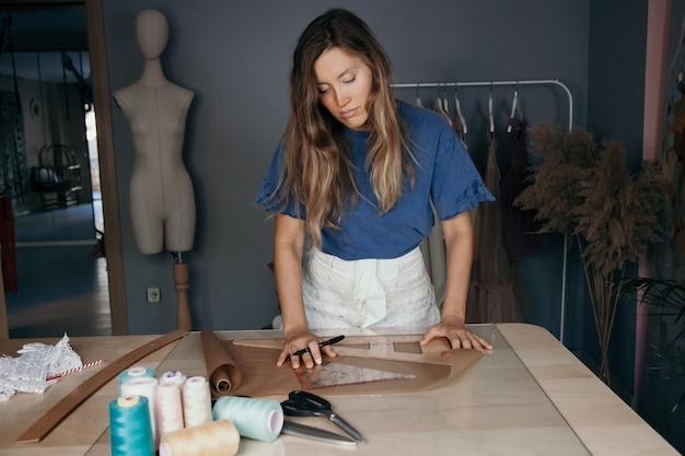 Mujer sonriente caucásica joven que mide un patrón de tela. concepto a medida. concepto de negocio de costura.