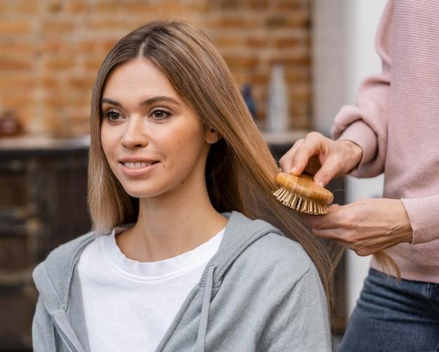 Mujer sonriente cepillarse el pelo en el salón