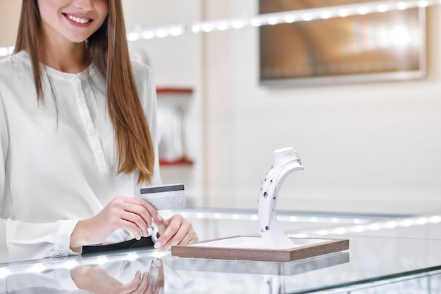 Mujer sonriente cerca del mostrador en una joyería tiene una tarjeta de crédito lista para pagar el collar