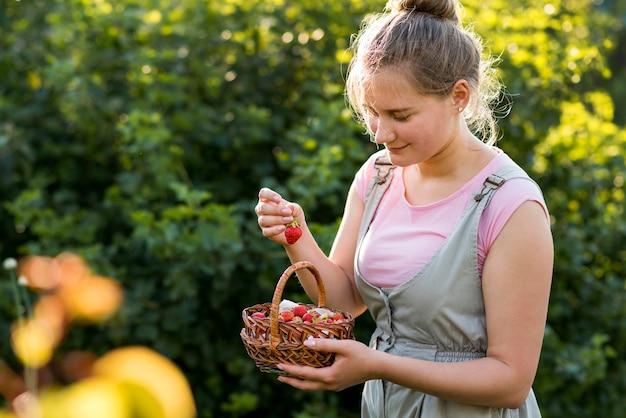 Mujer sonriente con cesta de fresas
