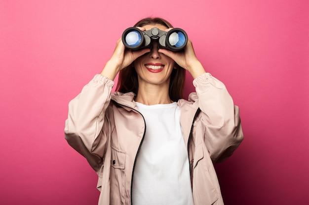 Mujer sonriente en chaqueta mirando a través de binoculares