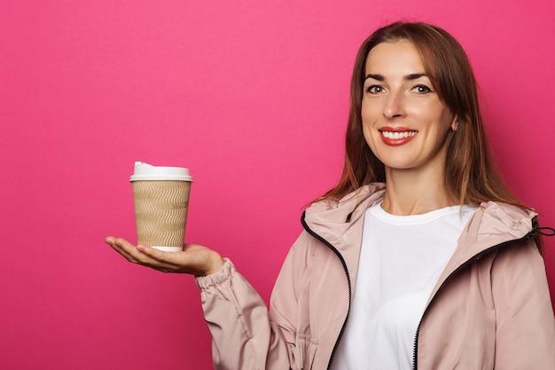 Mujer sonriente en chaqueta sosteniendo rollo de papel en la palma