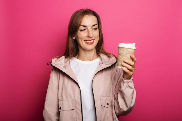 Mujer sonriente en chaqueta sosteniendo rollo de papel