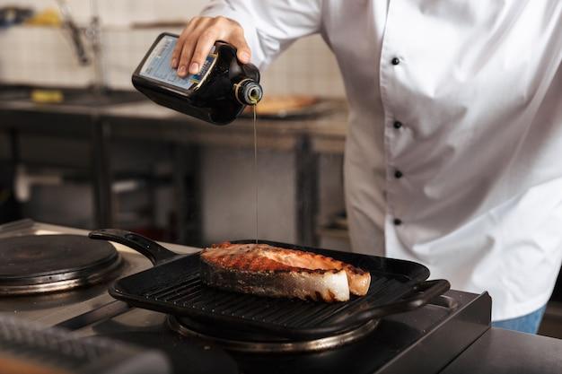 Mujer sonriente chef cocinero vistiendo uniforme cocinando delicioso filete de salmón de pie en la cocina, vertiendo aceite de oliva