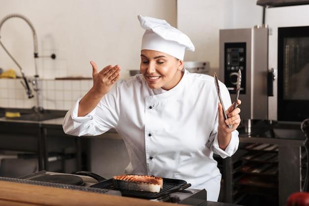 Mujer sonriente chef cocinero vistiendo uniforme cocinando delicioso filete de salmón de pie en la cocina