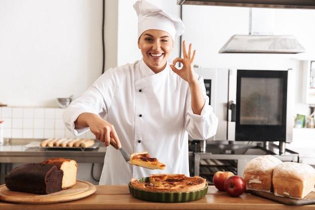 Mujer sonriente chef cocinero vistiendo uniforme mostrando pastel cocido mientras está de pie en la cocina
