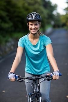Mujer sonriente ciclismo en la carretera