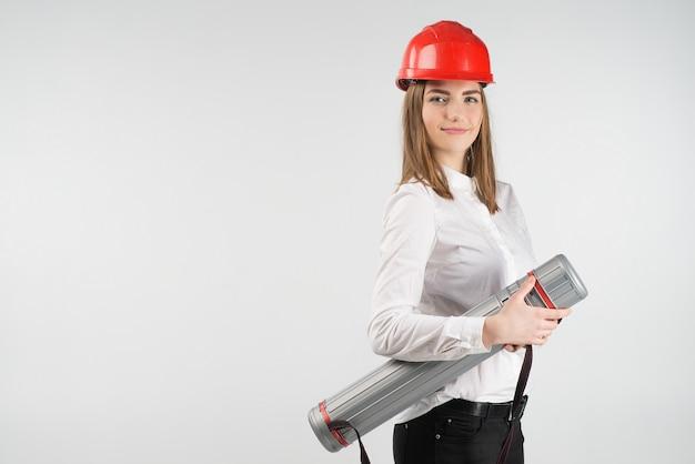 La mujer sonriente se coloca en el casco anaranjado sostiene el tubo. - lugar de texto.