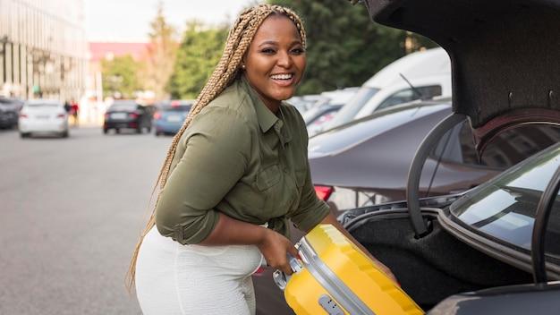 Mujer sonriente colocando su equipaje en su baúl