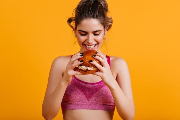 Mujer sonriente come hamburguesa