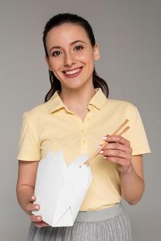 Mujer sonriente comiendo de caja de dibujos animados