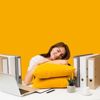 Mujer sonriente complacida de descansar su cabeza sobre almohadas encima del escritorio
