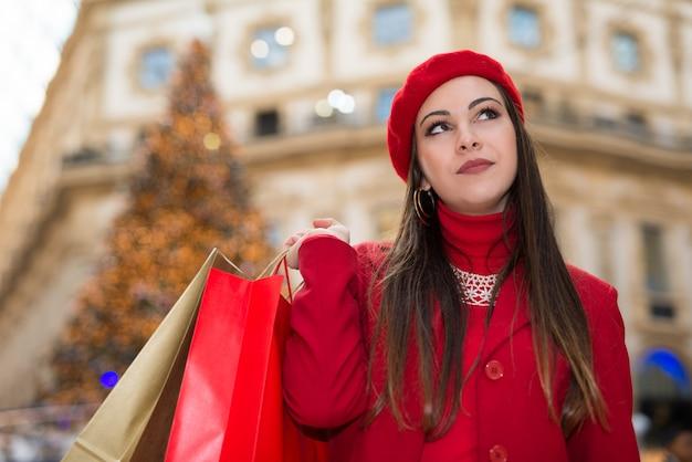 Mujer sonriente de compras en una ciudad antes de navidad