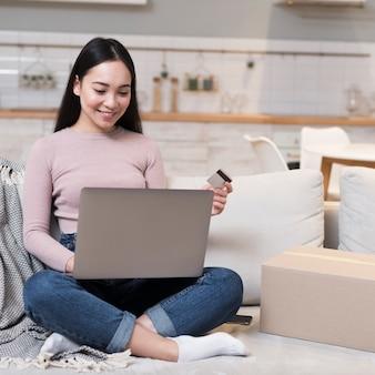 Mujer sonriente de compras en línea con laptop y tarjeta de crédito