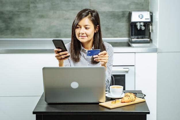 Mujer sonriente de compras en línea usando una computadora portátil y una tarjeta de crédito en casa