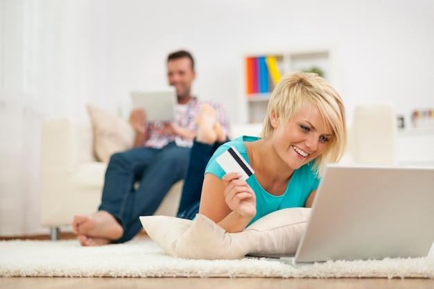 Mujer sonriente y compras online en casa