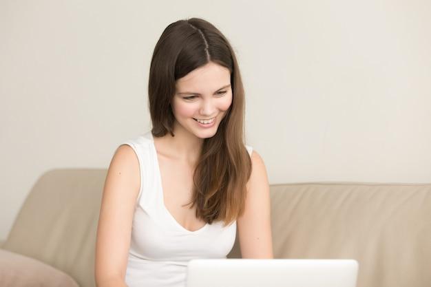 Mujer sonriente se comunica con amigo en internet