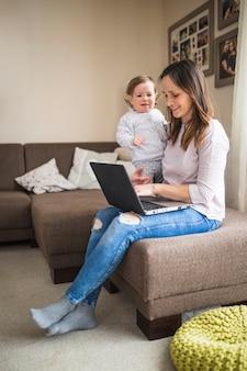 Mujer sonriente con su hija trabajando en la computadora portátil