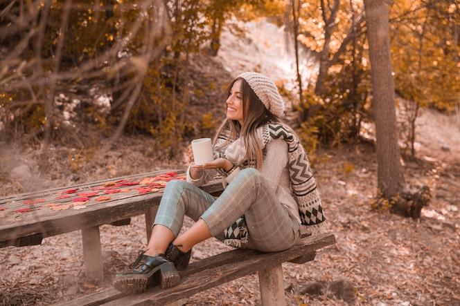 Mujer sonriente con taza cerca de la mesa en el parque