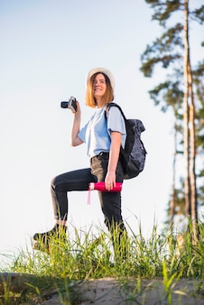 Mujer sonriente con termo y cámara