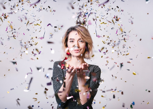 Mujer sonriente con confeti volando en la fiesta