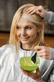 Mujer sonriente conseguir su cabello teñido por peluquero en casa