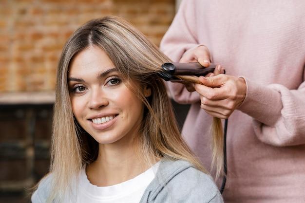 Mujer sonriente consiguiendo su cabello alisado en casa