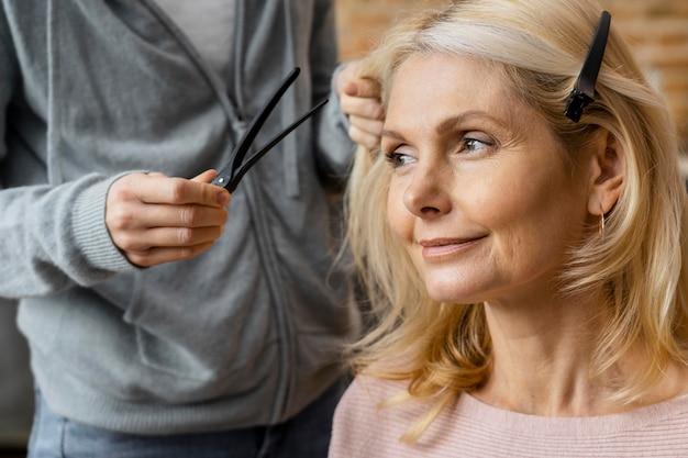 Mujer sonriente consiguiendo su peinado en casa