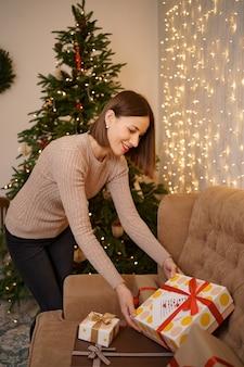 Mujer sonriente contando regalo de navidad en el sofá de la sala de estar cerca del árbol de navidad